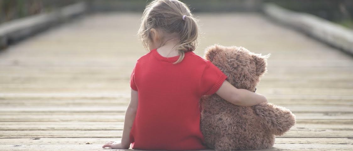 Little girl in a red dress sitting on a boardwalk hugging teddybear, view from behind